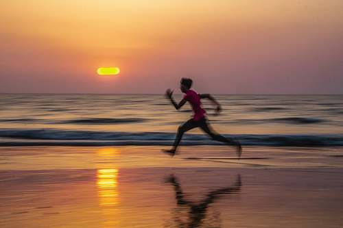 nature man running along seashore during golden hour water