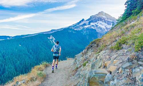 hiking man running on edge near mountain mountain