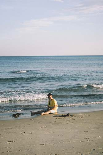 nature man sitting by the seashore during daytime ocean