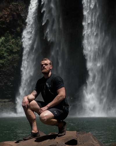 nature man sitting on rock near waterfalls river