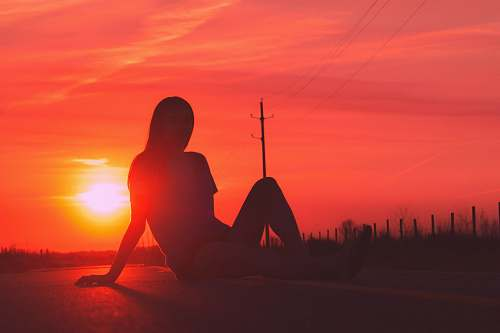 nature silhouette of woman sitting in road during golden hour sky