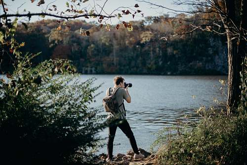 person man with backpack taking picture beside lake human