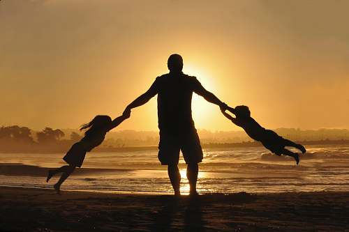family silhouette of man holding two childrens on shore during daytime silhouette