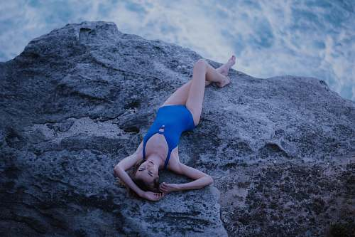 person woman lying on boulder neat water human