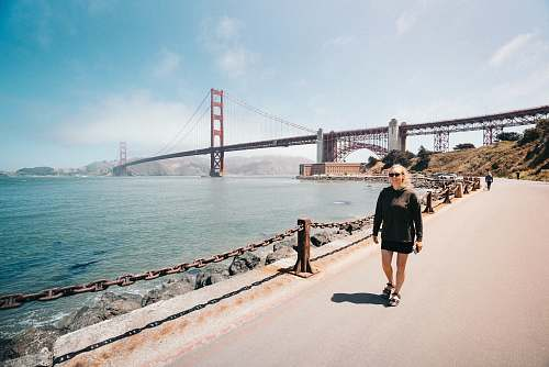 human woman walking near Golden Gate Bridge bridge