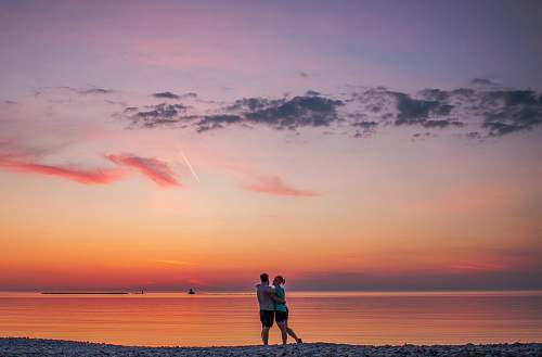 human couple hugging each other near seashore people