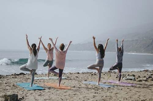 human five woman standing on seashore yoga