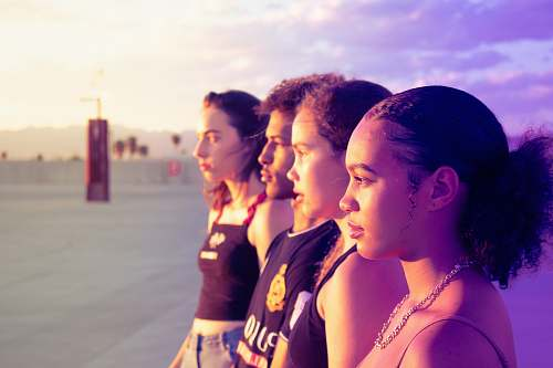 human four women standing on pathway looking side skin