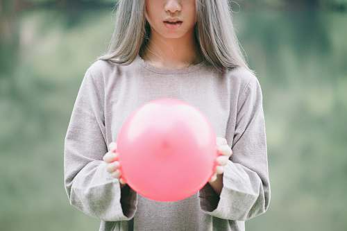 human girl in grey long-sleeved shirt holding pink balloon people