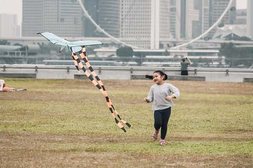 human girl swearing gray crew-neck long-sleeved shirt running in green field near orange and white plane kite viewing high-rise buildings sport