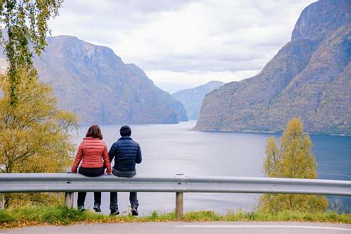 human man and woman sitting on road fence people