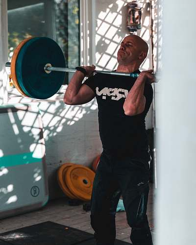 human man carrying barbell working out