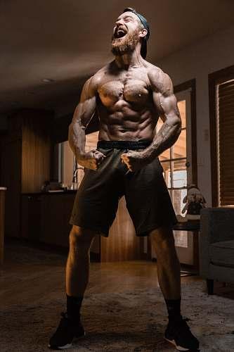 human man flexing muscles wood