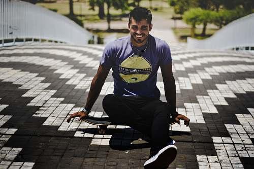 human man in gray t-shirt sitting on skateboard people