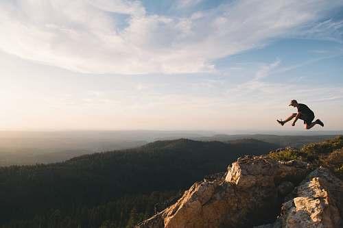 hiking man jumping on brown rock mountain during daytime mountain