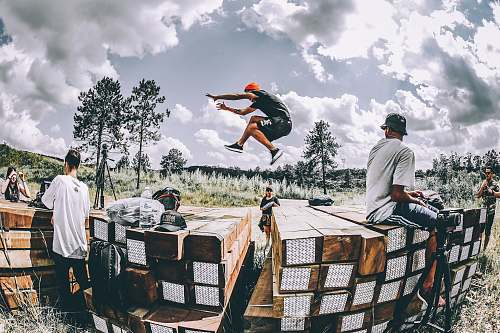 human man leaping on brown wooden platform people