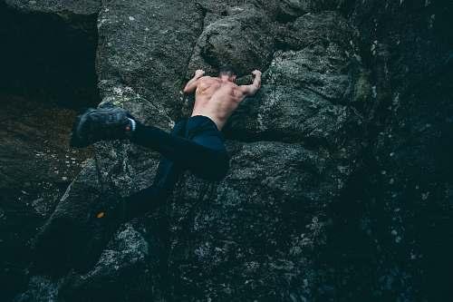 sport man rock climbing on gray rock climb
