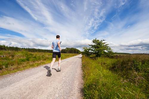 fitness man running on road near grass field exercise
