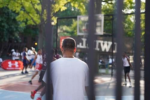 human man sitting on basketball court pedestrian