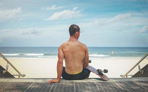 beach man sitting on gray surface holding skateboard ocean