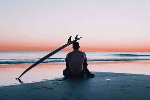 human man sitting on the sand in front of sea nature
