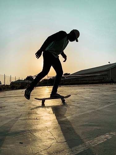 human man skateboarding on cemented vacant lot during sunset sport