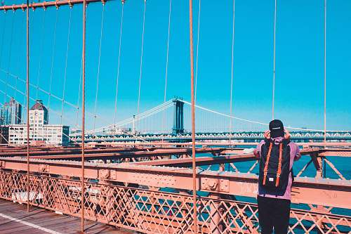 human man standing on Brooklyn bridge facing Manhattan bridge during daytime people