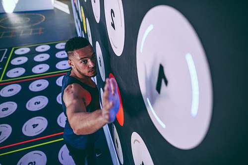 human man wearing black tank top climbing and about to reach number 1 sport