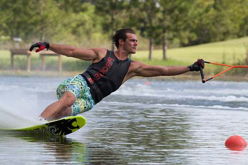 human man wearing gloves and black tank top while water skiing people