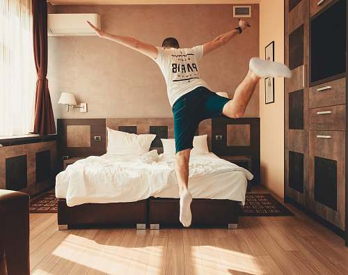 human man wearing white shirt about to jump on bed flooring