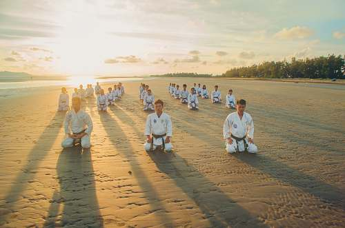 human people kneeling on sandy ground sports