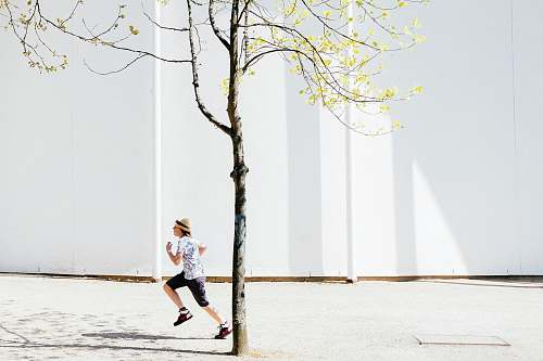 human person in white T-shirt running shorts