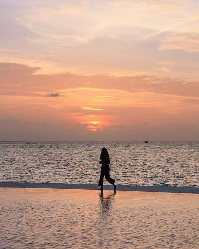 human person jogging on seashore under orange sky nature