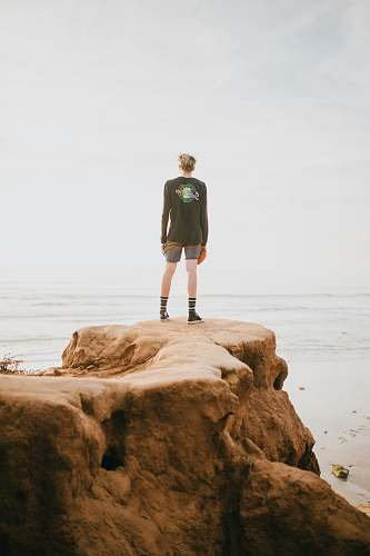 human person standing at the edge of a cliff in front of ocean during daytime people