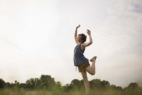 human person standing raising right leg as well as both hands apparel