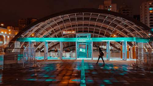 human person walking beside waiting shed with teal light at night time flooring