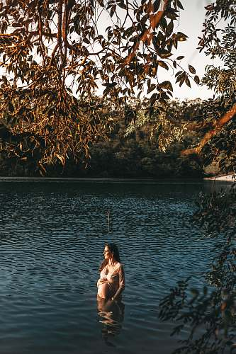 human pregnant woman standing in body of water during daytime water