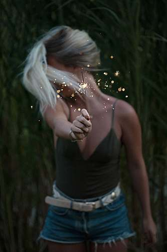 people selective focus photo of woman holding sparkler while looking away girl