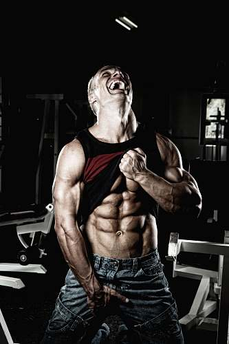 human smiling man holding up his black tank top and and blue denim bottoms while looking up fitness