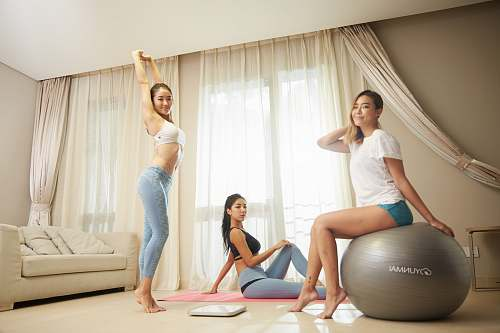 human three women doing exercise inside gray room people