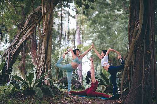 human three women doing yoga at forest people