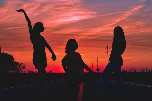 people three women posing in the middle of the road during golden hour human