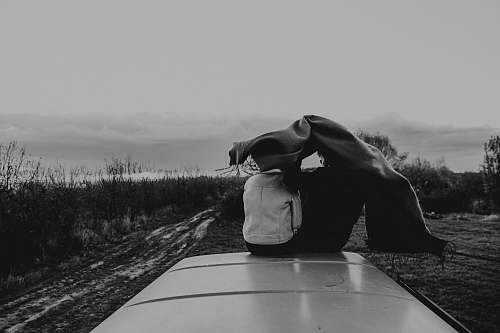 human two person sitting on top of vehicle grayscale photography black-and-white