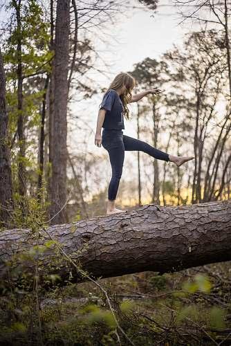 human woman balancing on log plant