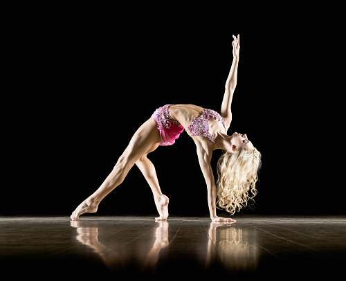 dance woman bending on floor and with black background ballet
