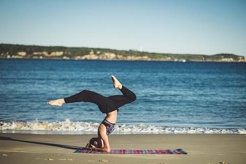 people woman doing yoga beside the seashore yoga