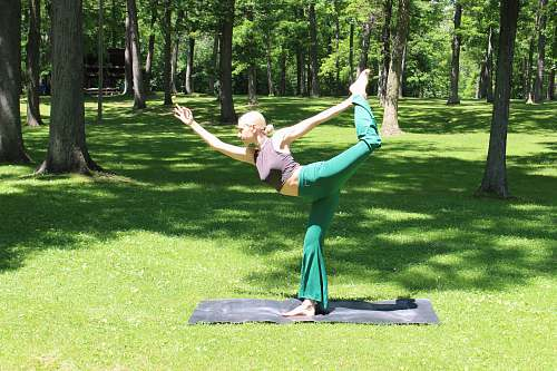 human woman doing yoga exercise outdoor grass