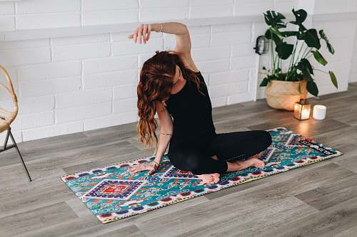 human woman doing yoga inside room furniture