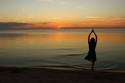 fitness woman doing yoga near calm body of water during golden hour sports