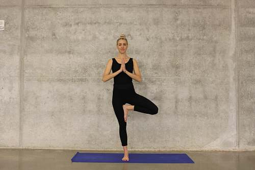 human woman in black attire doing one foot stance yoga yoga